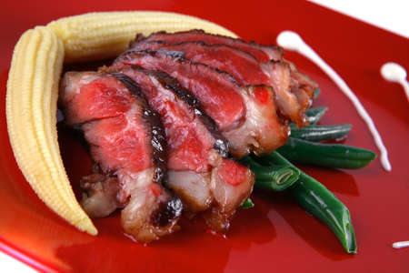 meat served with beans and corns on red plate photo