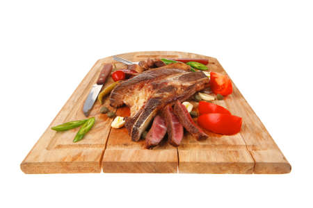fresh grilled beef meat fillet sliced on wooden board with tomatoes and red pepper and cutlery isolated  over white background photo