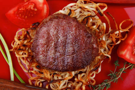 grilled beef fillet pieces on noodles , red hot chili pepper with tomato on red plate over wood table photo