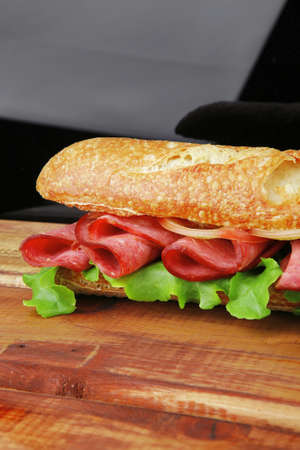french long baguette with smoked chicken sausage on wood over black photo