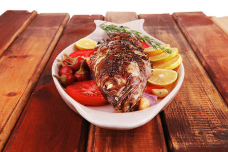 fryed: savory: whole fryed sunfish over wood with tomatoes lemons and peppers Stock Photo