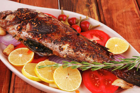savory: whole fryed sunfish over wood with tomatoes lemons and peppers Stock Photo - 14945853