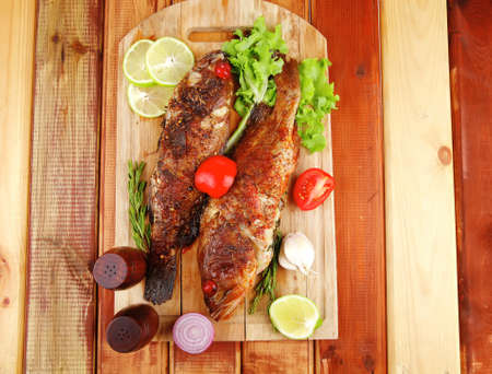 savory on wooden table: two fried fish served with tomatoes and castors photo