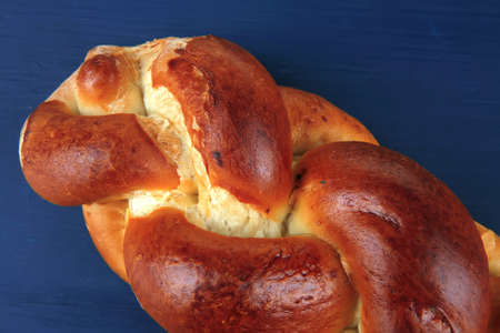 baked product : golden challah on blue wooden table photo