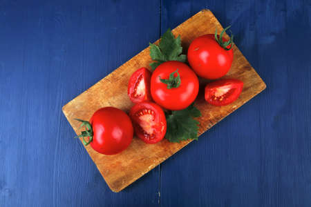 raw vegetables : some uncooked ripe fresh tomatoes on cutting board  ready to cooking over blue table photo