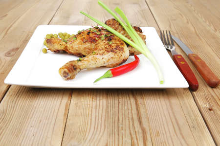 meat food : chicken legs garnished with green peas and hot chili peppers on white plates over wooden table photo
