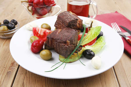 meat savory : beef fillet mignon grilled and garnished with baked apples , tomatoes and juice on wooden table photo