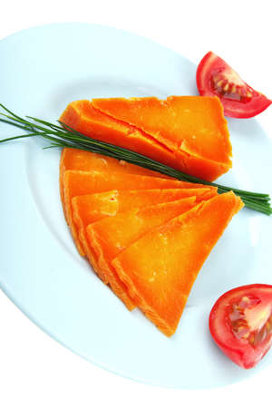 sustained: orange aged delicious cheddar cheese chop with slice on blue plate with tomatoes and chives isolated over white background
