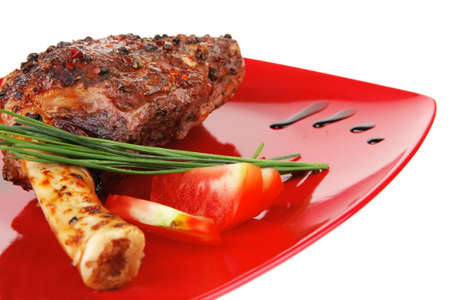 entree: savory plate : roasted meat shoulder on red plate with chives and tomato isolated on white