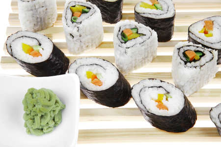 philadelphia roll: Roll with Cucumber , Cream Cheese with raw Tuna and Salmon inside. on wooden grid . Isolated over white background . Japanese traditional Cuisine
