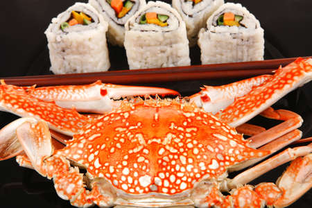 Roll with Cucumber , Cream Cheese with raw Tuna and Salmon inside. on black dish with boiled crab . Japanese traditional Cuisine photo
