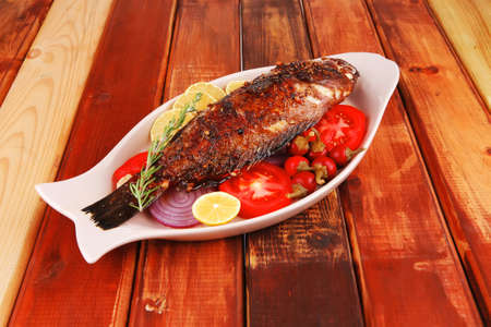 main course: whole fryed sunfish on wooden table with lemons and peppers Stock Photo - 15008814