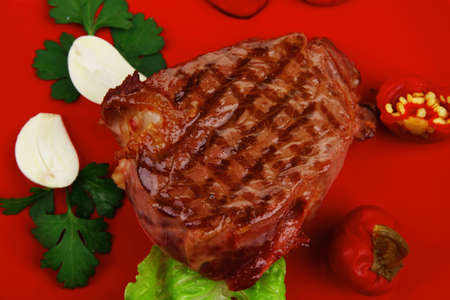bbq : beef (pork) steak garnished with green lettuce and red chili hot pepper on red plate isolated over white background Stock Photo - 15011612