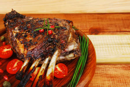 grilled ribs on wooden table with vegetables photo