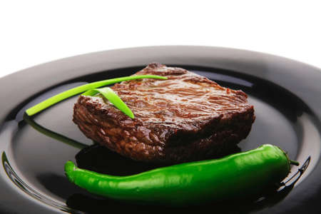 meat savory : grilled beef fillet mignon served on black plate isolated over white background with chili pepper photo