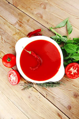 diet food : hot tomato vegetable soup with basil thyme and raw tomatoes in white round bowl over red mat on wood table ready to eat photo