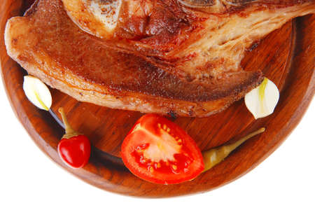 hot red beef meat steak on red wooden plate with capers and tomatoes isolated over white background photo