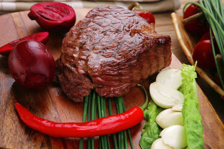 bbq : beef (pork) steak garnished with green staff and red chili hot pepper on wooden table with cutlery Stock Photo - 15051821