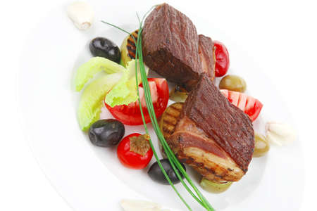 grilled meat : beef ( lamb ) garnished with tomatoes , green and black olives on white plate isolated over white background photo