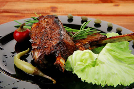 cooked pepper ball: served meat: spiced barbecued ribs on black plate with vegetables