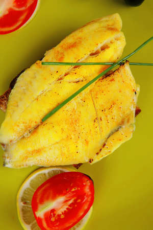 served roast golden fish fillet over wooden table with tomatoes and olives photo