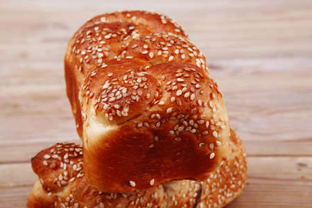 fresh loaf of light wheat bread topped by sesame seeds over wooden table photo