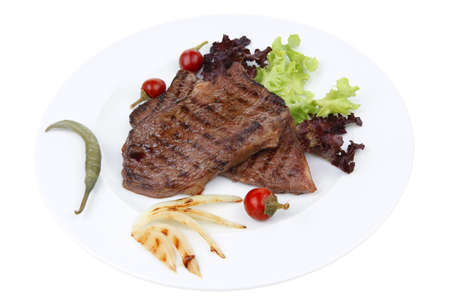 meat food : two roast steak boneless with red and chili peppers, served on green lettuce salad on dish isolated over white background Stock Photo
