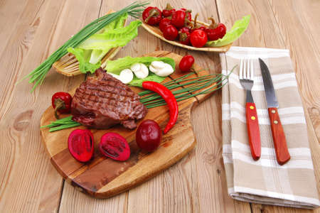 barbecued meat : beef ( lamb ) garnished with green lettuce and red chili hot pepper on wooden table with cutlery Stock Photo - 15677649
