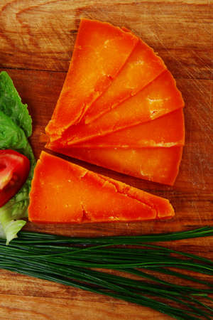 sustained: orange aged delicious cheddar cheese chop with slice on wooden plate with tomatoes , chives and salad . isolated over white background