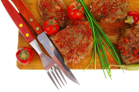 meat chops served with cutlery on wooden plate photo