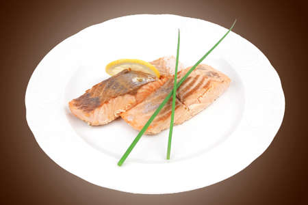 sea food : roasted pink salmon fillet with chinese onion, and lemon on white dish isolated over white background photo