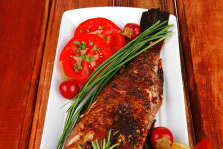 fryed: savory on wood: whole fryed sunfish over plate with tomatoes lemons and peppers