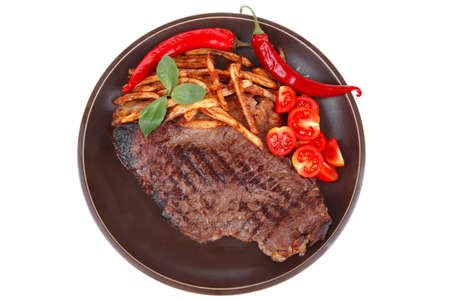 meat food : big grill beef steak on dark plate with red hot chili pepper and raw cherry tomato isolated on white background photo