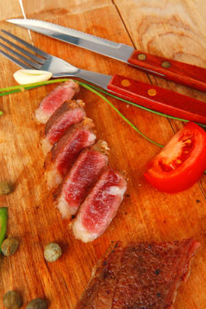 red meat steak sliced on wooden board with cutlery isolated  over white background photo