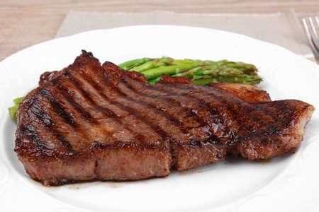 mesa de carne: asado medio raro filete de ternera con espárragos servidos en un plato blanco con cubiertos sobre la mesa de madera
