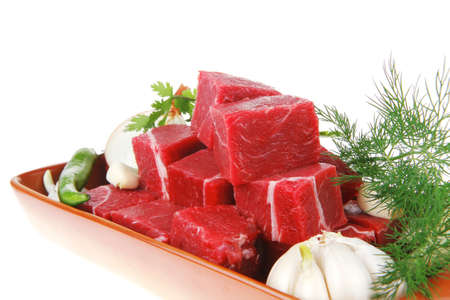 slices of raw fresh beef meat fillet in a ceramic dish with onions and peppers isolated over white background
