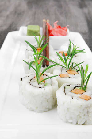 Maki Sushi - California Roll with Cucumber , Cream Cheese and Salmon inside. Served with wasabi and ginger . on long white plate over black table Stock Photo - 15729365
