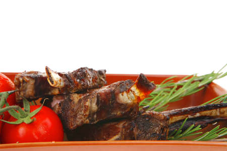 cooked pepper ball: meat portion : ribs on plate served with fresh cherry tomatoes and raw vegetables and chives Stock Photo