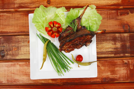 savory plate over wooden table: grilled ribs on white plate with chives, red hot peppers lettuce photo