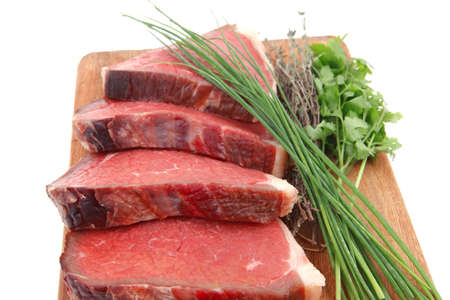 fresh ripe marble beef meat on wooden plate with thyme and chives isolated on white background photo