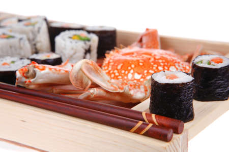 sake maki: Roll with Cucumber , Cream Cheese with raw Tuna and Salmon inside. on wooden plate with live crab  . Isolated over white background . Japanese traditional Cuisine