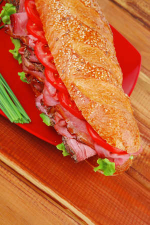pepper castor: french sandwich : fresh white baguette with chicken smoked sausage on red ceramic plate over wooden table