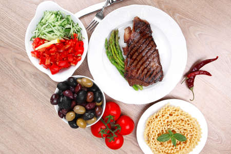meat table : grilled beef fillet with asparagus , pasta portion , tomatoes and several kinds of olives served on white dish over light wood photo