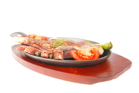 fresh grilled beef meat fillet on metal iron pan with tomatoes and red pepper isolated on white background photo