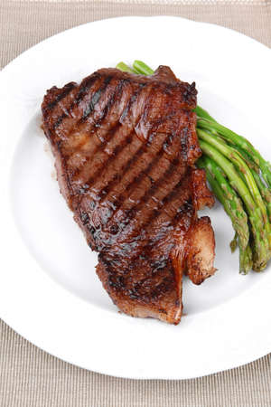 meat table : grilled beef fillet with asparagus served on white plate with cutlery over wooden table Stock fotó