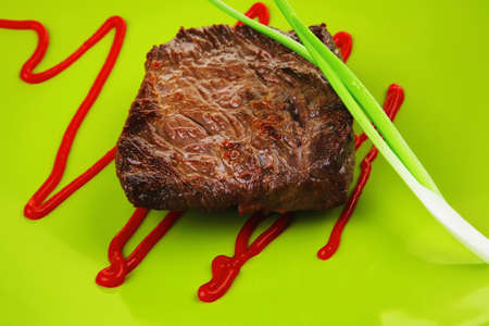 meat savory : grilled beef fillet mignon served on green plate isolated over white background with chives and ketchup photo