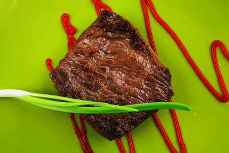 meat food : roasted fillet mignon on green plate with chives and ketchup isolated over white background photo