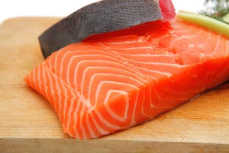 atun: salmón fresco sin cocer y rojas piezas de atún servido sobre tabla de madera aislada en el fondo blanco Foto de archivo