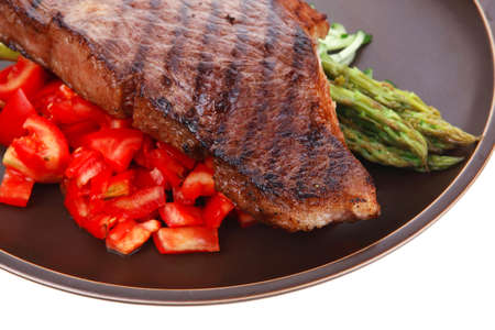 steak plate: meat table : grilled beef fillet with asparagus and tomatoes served on dish isolated over white