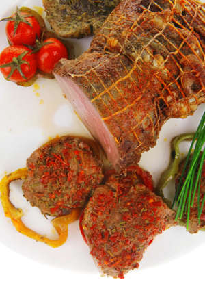 meat with chives and tomatoes over white plate photo